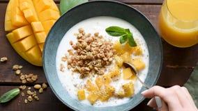 Movimento lento che mangia yogurt con il mango ed il granola archivi video