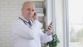 Movimento lento com o doutor na fatura de armário médica um telefonema usando as mãos livres filme