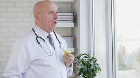 Movimento lento com o doutor no armário médico que toma uma pausa e que come um Apple filme