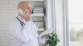 Movimento lento com um doutor na fatura de armário médica um telefonema usando a linha terrestre vídeos de arquivo