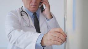 Movimento lento com um doutor Talking ao telefone celular e pesquisa de contratos médicos filme
