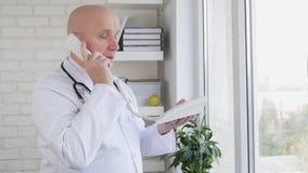 Movimento lento con il dottore Gesturing e parlare facendo uso della linea telefonica stock footage