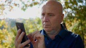 Movimento lento con l'uomo d'affari Text Using Cellphone sulla via archivi video