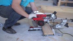 Movimento lento da beleza woodworking na casa - um homem profissional novo monta um assoalho da madeira de pinho vídeos de arquivo