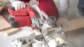 Movimento lento da beleza woodworking na casa - um homem profissional novo monta um assoalho da madeira de pinho filme