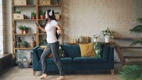 Movimento lento da dança asiática bonito e do salto da senhora no assoalho de fones de ouvido vestindo do apartamento moderno, gu filme