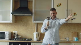 Movimento lento da dança engraçada nova atrativa do homem e canto com concha ao cozinhar na cozinha em casa vídeos de arquivo