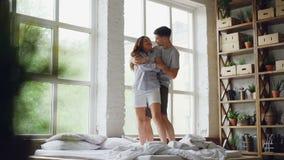 Movimento lento da dança loving adorável dos pares na cama e do aperto junto na casa clara moderna Jovens felizes filme