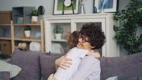 Movimento lento da mãe de amor e do filho pequeno que abraçam o assento no sofá em casa vídeos de arquivo