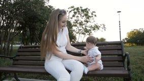 Movimento lento da mãe e da filha que sentam-se no banco no parque vídeos de arquivo