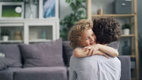 Movimento lento da mãe emrbacing do rapaz pequeno bonito com amor e ternura