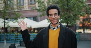 Movimento lento da mão de ondulação do indivíduo afro-americano amigável que sorri fora vídeos de arquivo