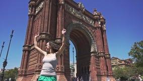 Movimento lento da menina alegre e bonita que gira ao redor contra Arco de Triomf filme