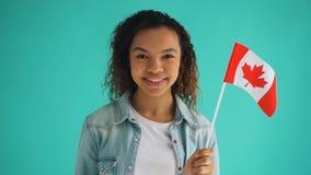 Movimento lento da menina canadense da raça misturada do cidadão que guarda o sorriso da bandeira nacional vídeos de arquivo