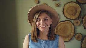 Movimento lento da menina consideravelmente loura na parte superior na moda do chapéu e da sarja de Nimes que olha a câmera, o so filme