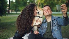 Movimento lento da menina feliz e do indivíduo dos pares que tomam o selfie com o cão bonito que levanta e que beija o animal que filme