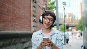 Movimento lento da menina que escuta a música no fones de ouvido usando o smartphone fora vídeos de arquivo