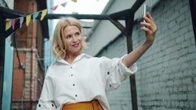 Movimento lento da mulher envelhecida consideravelmente média que toma o selfie com smartphone fora filme