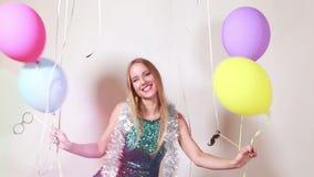 Movimento lento da mulher loura feliz que salta com os balões na cabine da foto video estoque