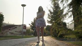 Movimento lento da mulher que anda através da cidade no pavimento de atrás filme