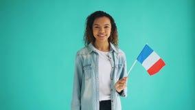 Movimento lento da senhora francesa da raça misturada que acena a bandeira oficial e o sorriso vídeos de arquivo