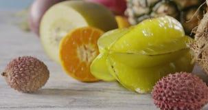 Movimento lento da zorra do close-up do fruto de paixão, carambola, lichi em um fundo de madeira Conceito de comer da dieta do ve filme