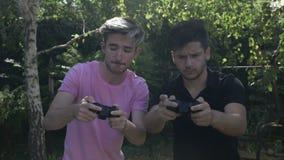 Movimento lento de dois amigos novos viciado ao jogo video que joga com controladores em uma parte externa do parque - filme