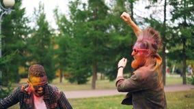 Movimento lento de homens novos engraçados nos óculos de sol com as caras pintadas que dançam e que riem fora no festival de Holi vídeos de arquivo
