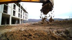 Movimento lento de um escavador que escava um poço e que joga a sujeira Close-up de uma cubeta da máquina escavadora que jogue pa vídeos de arquivo