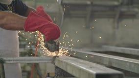 Movimento lento de um trabalhador que usa o moedor do metal com as faíscas que voam em uma loja do metal vídeos de arquivo