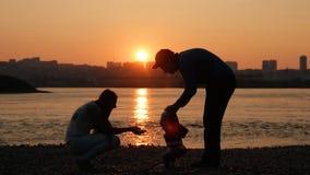 Movimento lento de uma família nova que anda pelo rio no por do sol vídeos de arquivo