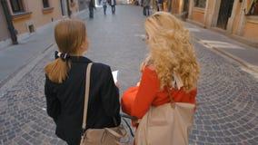 Movimento lento de uma opinião traseira duas jovens senhoras que andam e que falam filme