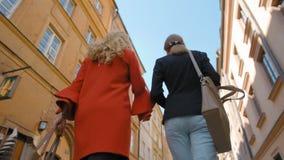 Movimento lento de uma opinião traseira duas senhoras Touristss que anda e que fala na cidade video estoque