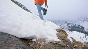 Movimento lento de uma senhora Wading um córrego e um salto da montanha à superfície da àgua no inverno vídeos de arquivo