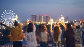 Movimento lento degli amici felici della gioventù che tengono le stelle filante e che muovono le mani sollevate che stanno sul te archivi video