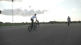 Movimento lento dei motociclisti freschi sulla via che esercitano i loro trucchi acrobatici di stile libero - archivi video
