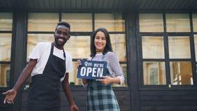 Movimento lento dei proprietari felici del caffè della gente che tengono segno aperto e che esaminano costruzione dietro loro poi video d archivio