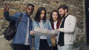 Movimento lento dei turisti maschii e femminili che esaminano mappa che sta nella via e che parla cercando modo durante il viaggi video d archivio