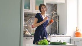 Movimento lento del ballo divertente del cuoco della donna con lattuga verde mentre cucinando nella cucina a casa archivi video