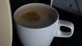 Movimento lento del caffè di esspresso che versa dalla macchina alla tazza bianca video d archivio