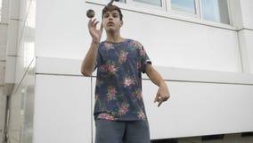 Movimento lento del giocattolo di turbine di kendama del giovane ragazzo con la sua mano che esercita un movimento avanzato - video d archivio
