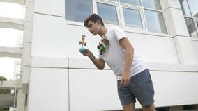Movimento lento del giovane che esercita trucco di kendama dell'equilibrio del confine all'aperto nel cortile della scuola - archivi video