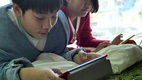 Movimento lento del ragazzo felice e della ragazza asiatici che giocano gioco sul computer della compressa insieme al fronte di s stock footage