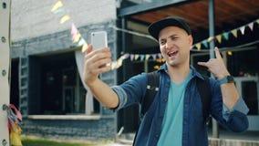 Movimento lento dell'uomo allegro che prende selfie all'aperto facendo uso della macchina fotografica dello smartphone video d archivio