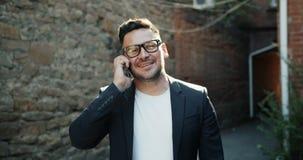 Movimento lento dell'uomo d'affari felice che parla sul telefono cellulare all'aperto che sorride archivi video