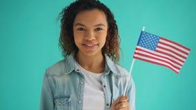 Movimento lento della bandiera americana della tenuta della ragazza della corsa mista che sorride sul fondo blu archivi video