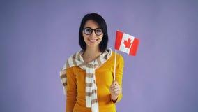 Movimento lento della bandiera nazionale canadese della tenuta dei pantaloni a vita bassa che sorride esaminando macchina fotogra archivi video