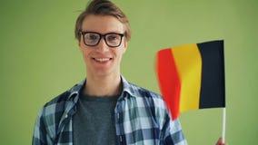 Movimento lento della bandiera della tenuta del patriota dello studente maschio della Germania e di sorridere stock footage