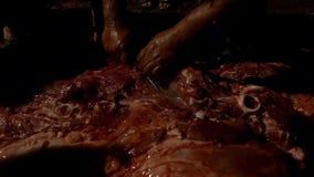Movimento lento della carcassa di maiale della pelle dei tagli dell'uomo nel macello all'azienda agricola di notte della via stock footage