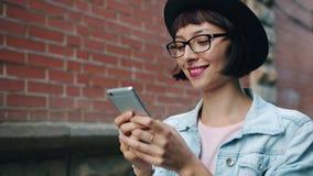 Movimento lento della donna allegra che utilizza smartphone moderno che cammina all'aperto nella città archivi video